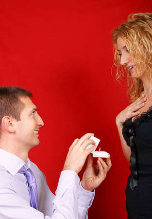 A man proposing marriage to her girlfriend, who is astonished. Studio shoot over red background.