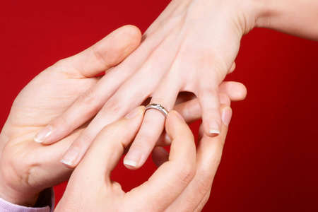 proposal: Man putting an engagement ring on a womans hand over red background