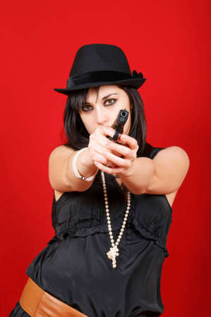 Portrait of a young woman wearing a black hat and pointing a gun to the camera. Studio shot over red background. Stock Photo