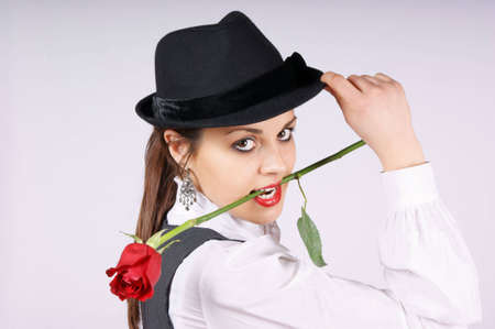 Portrait of a beautiful young woman wearing white blouse, black pinstriped gilet and black hat. The woman is holding a red rose in mouth while looking at camera.