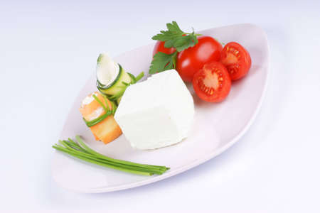 Cream cheese, Piccadilly tomatoes, zucchini and carrot rolls with cream cheese finely disposed on a white plate.