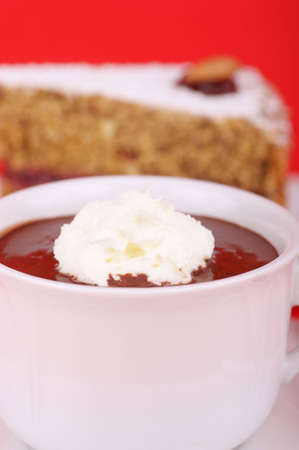 A cup of hot chocolate with whipped cream and a piece of buckwheat cake in the background. Selective focus. Extremely shallow DOF. Stock Photo