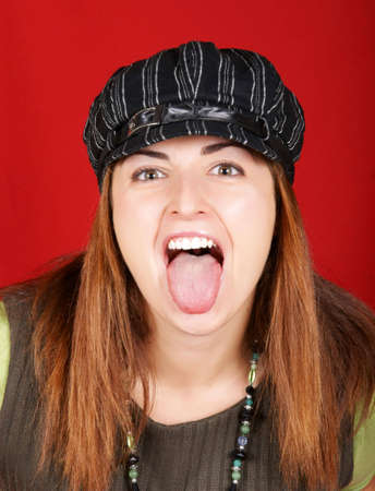 girl tongue: Portrait of a young girl sticking out her tongue over red background Stock Photo