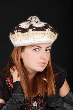 Beautiful young woman wearing a wool, knit cap. Studio shot over black background. Stock Photo - 7004660