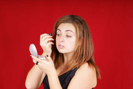 eye liner: Portrait of a young woman applying liquid eye liner. Studio shot over red background. Stock Photo