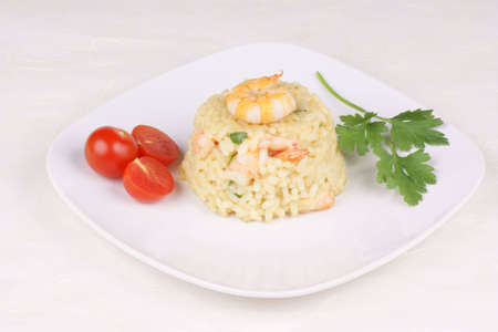 Risotto with shrimps served on a white plate. Studio shot, shallow DOF.