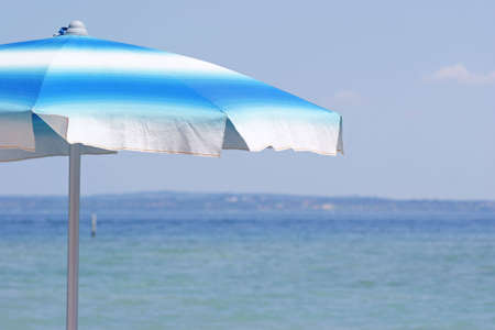white and blue striped beach umbrella at Garda lake (Italy) Stock Photo