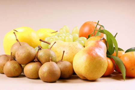 Assortment of autumn fruits on light brown background Stock Photo