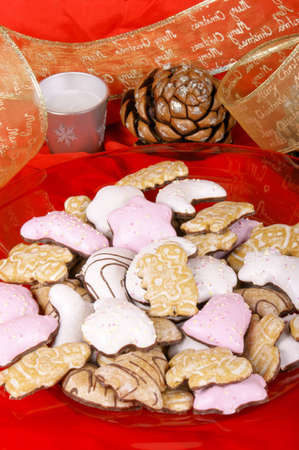 Assorted Christmas gingerbread cookies on a red plate and Christmas decorations over a red background Stock Photo