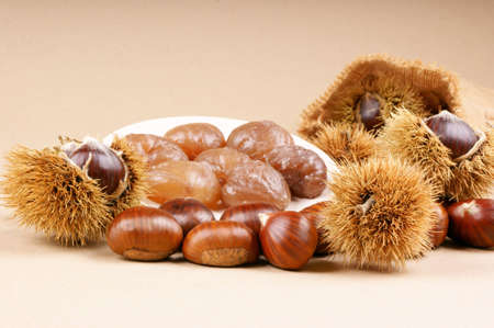 Chestnuts and marron glacé over a light brown background Stock Photo