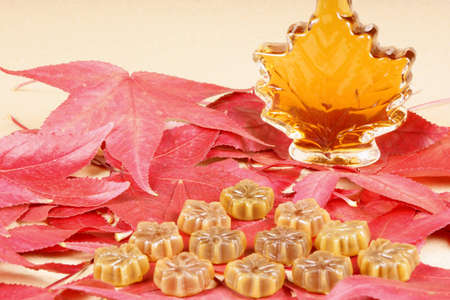 Maple syrup and maple syrup candies on a bed of maple leaves