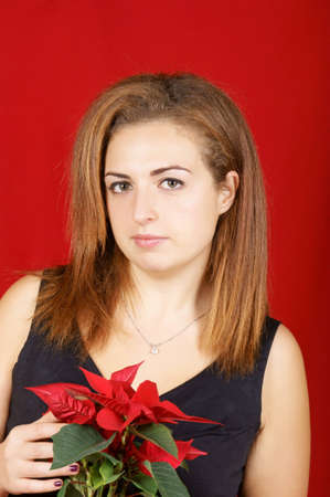 Portrait of a beautiful young girl wearing a black dress and holding a red Poinsettia. Studio shot over red background photo