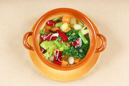 Homemade typical italian minestrone (vegetable soup) in a rustic ceramic bowl. Studio shot over light brown background.