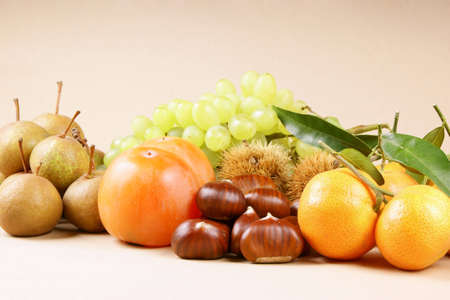 asian pear: Assortment of autumn fruits over a light brown background