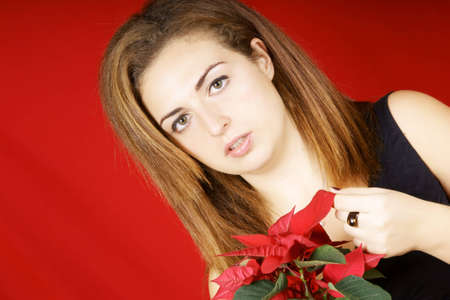 Portrait of a beautiful young girl holding a red Poinsettia over red background photo