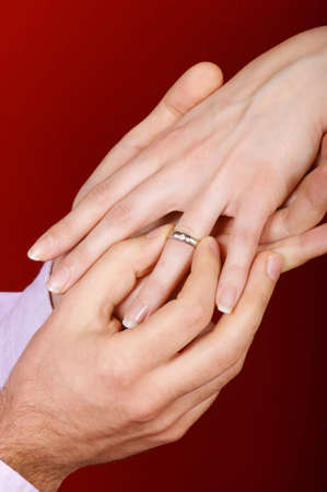 engagement ring: Man putting an engagement ring on a womans hand over red background