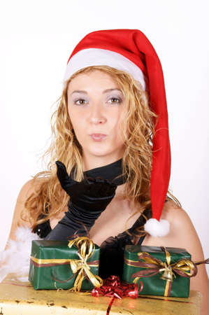 Beautiful young girl whit Santa hat blowing a kiss and holding presents photo
