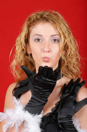 Portrait of a beautiful young girl wearing black gloves with feathers and blowing a kiss toward the camera photo
