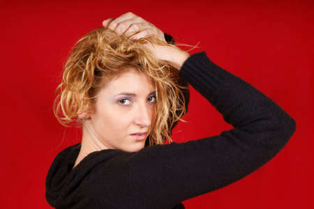 Portrait of an attractive young woman wearing a black pullover and holding her hair up. Studio shot over red background. photo