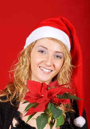 Beautiful young girl wearing Santa hat and holding a red Poinsettia over red background photo