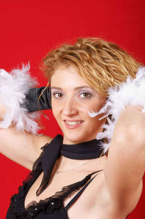Portrait of a beautiful blond young woman with a black shirt, black scarf and black gloves with feathers. She is looking at camera and holding up her hair. Studio shot over red background. photo