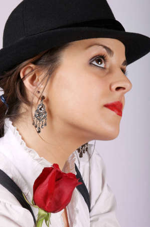 Portrait of a sexy young woman wearing a black hat and holding a red rose. Studio shot. Stock Photo - 7601822