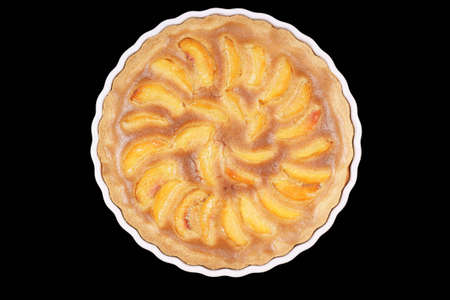 Peach tart in a white pottery cake tin. Isolated on black background Stock Photo