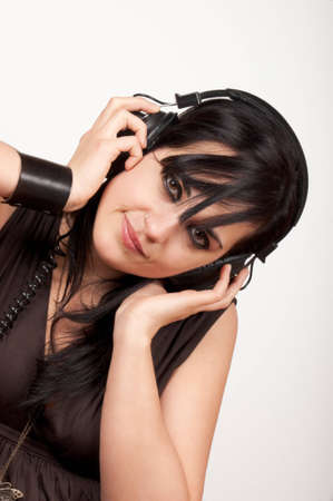 Beautiful young woman wearing headphones and listening to the music. Studio shot. Stock Photo - 8110165