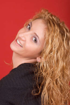Beautiful young woman looking over shoulder and smiling. Studio shot over red background photo