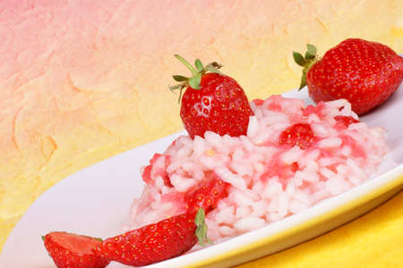 Rice with strawberries served on a white dish. Studi shot over a yellow-red background Stock Photo