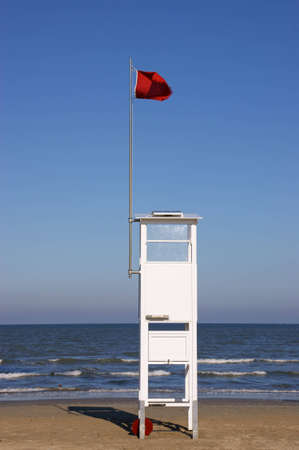 Lifeguard tower on the beach with a red warning flag
