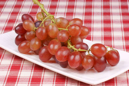 Italian red table grape on a white plate. Stock Photo