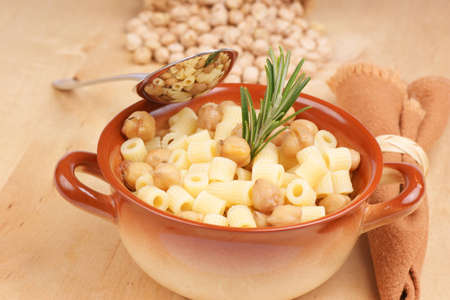 Small thimbles (ditalini) with chickpea and rosemary served in a ceramic bowl. Shallow DOF photo