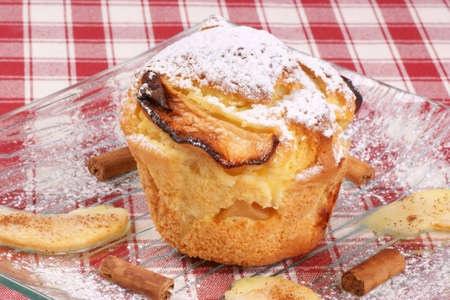 Apple muffin served on a glass plate with icing sugar, cinnamon and apple slices