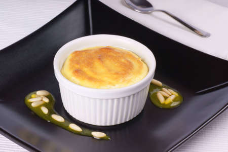 Lemon ricotta souffle in a white ramekin served on a black plate