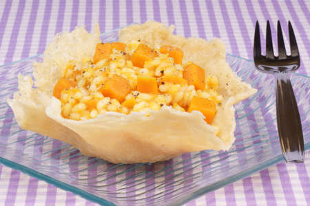 Cheese basket filled with risotto and pumpkin over a glass dish Stock Photo