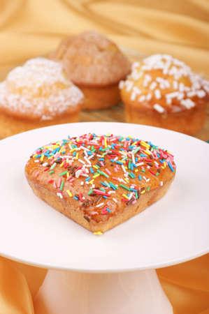 Bollo en forma de corazón en un stand de pastel y panecillos surtidos fuera de foco en segundo plano. Enfoque selectivo, DOF superficial Foto de archivo - 9543372