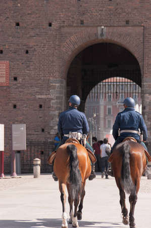 Milan, Italy - April 7, 2011: Two policemen on horseback at the entrance of Castel Sforzesco in Milan Editorial
