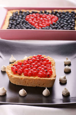 samll: Heart-shaped tart with redcurrants served on a black plate decorated with samll meringues. Tart with berries out of focus in the background. Selective focus, shallow DOF Stock Photo