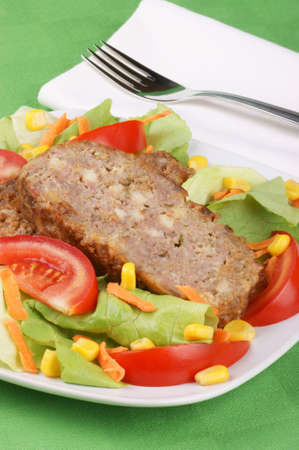 Slices of meatloaf served on a white plate with fresh mixed salad Stock Photo - 10776065