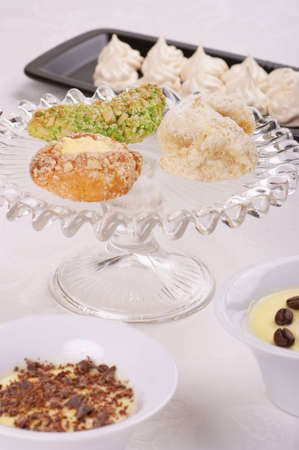 Typical sicilian almond cookies served on a glass cake stand. Cream servings with chocolate flakes and coffee beans are out of focus in the foreground. Meringues on a black plate are out of focus in the background. Selective focus, shallow DOF photo