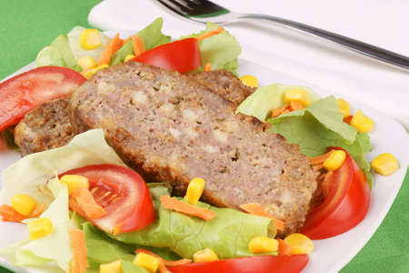 Slices of meatloaf served on a white plate with fresh mixed salad. Selective focus, shallow DOF
