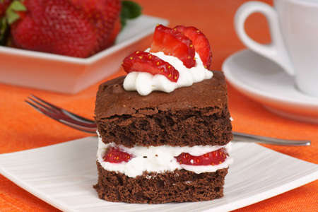 Fancy strawberry brownie with whipped cream served on a white plate  Strawberries and a coffee cup are out of focus in the background