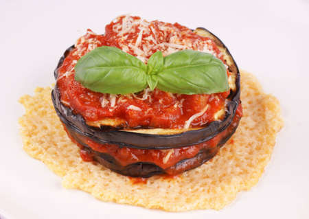 Parmigiana di melanzane   Aubergine parmigiana  over a cheese disk decorated with fresh basil