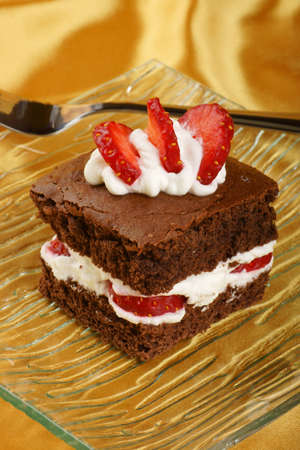 Fancy strawberry brownie with whipped cream served on a glass plate Stock Photo
