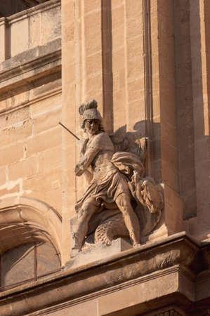 Statue of Saint Michael and the dragon on a church facade in Granada