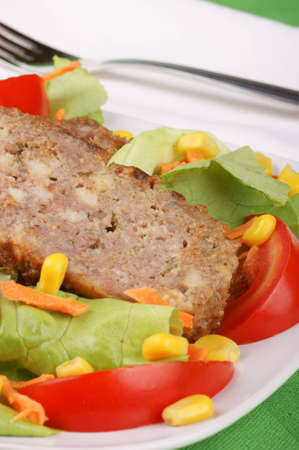 sudio: Slices of meatloaf served on a white plate with fresh mixed salad