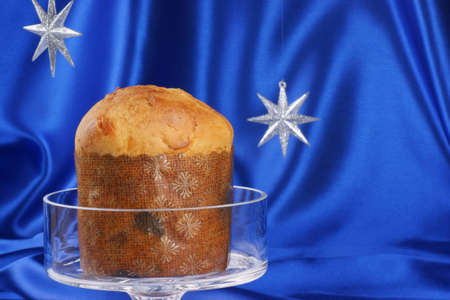 Christmas composition over a bright blue background  Panettone, a typical italian Christmas cake, served on a glass cake stand  Stock Photo