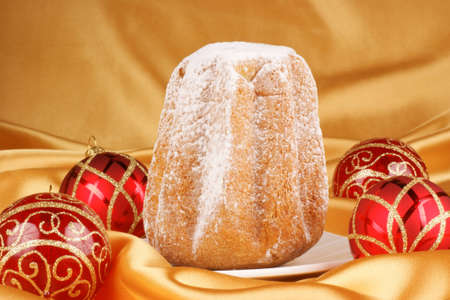 Christmas composition over a golden background  Pandoro, a typical italian Christmas cake, and Christmas decorations Stock Photo