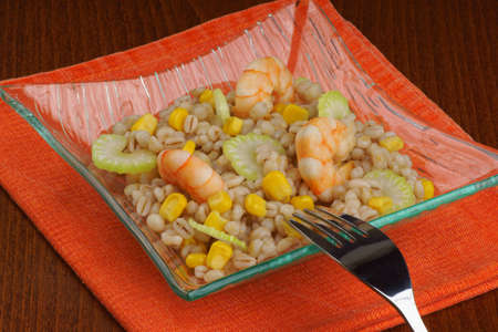 Pearl barley salad with shrimps served in a glass plate Stock Photo